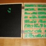 Es un instrumento de cálculo y consiste en una caja de madera dividida en 6 compartimentos para alojar los tipos numéricos. Mediante la combinación de los distintos tipos se realiza toda clase de operaciones aritméticas con extraordinaria facilidad de manejo. Consta de una rejilla de plástico con 36 x 27 espacios lo que hace un total de 972 celdillas, 270 tipos numéricos de plástico rígido de 17 x 5 mm, con signos braille en la base.